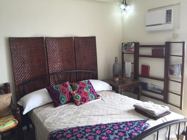 Queen size bed, with bamboo couch and rattan blinders all create a cozy atmosphere to enjoy