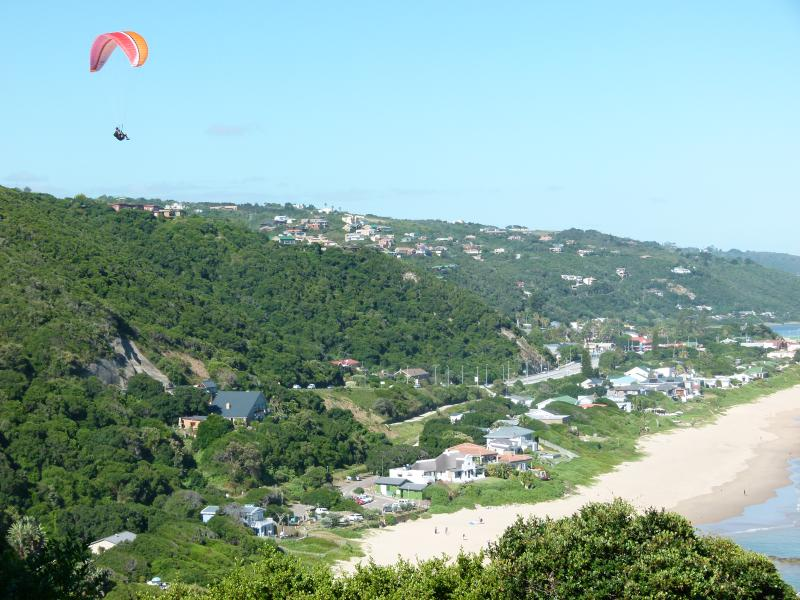 Paragliding with beach landing. Wilderness village in the background