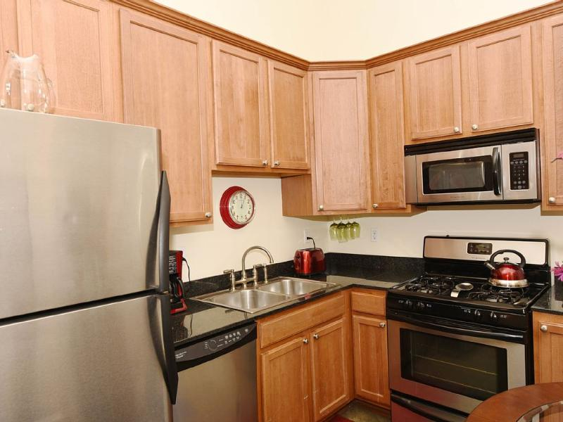 Fully equipped kitchen includes stainless appliances, toaster, coffeemaker, dishes, cookware.