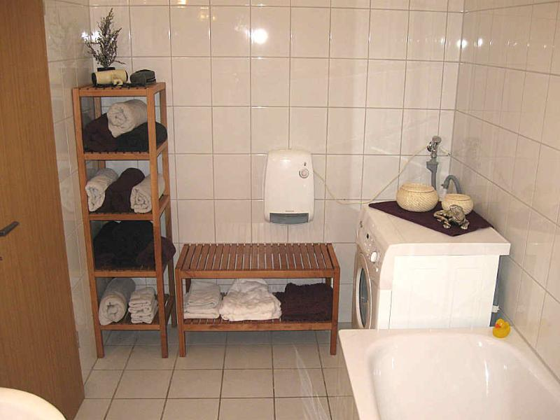 bathroom with tub and shower washing machine