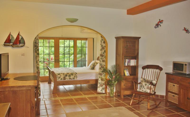 The main bedroom has sliding doors leading to a patio area. A barbecue is nearby