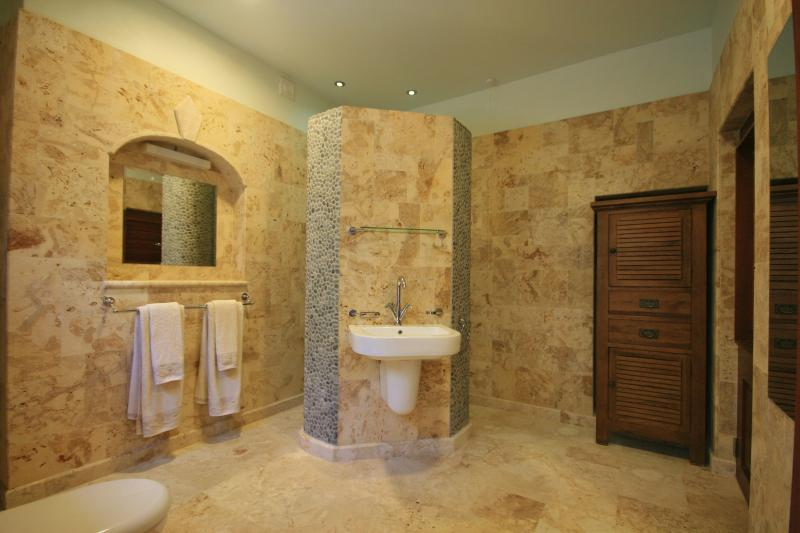 This very large and luxurious bathroom is tiled with natural Coral