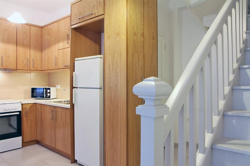 Hallway with large cabinet and door behind it to first bathroom.