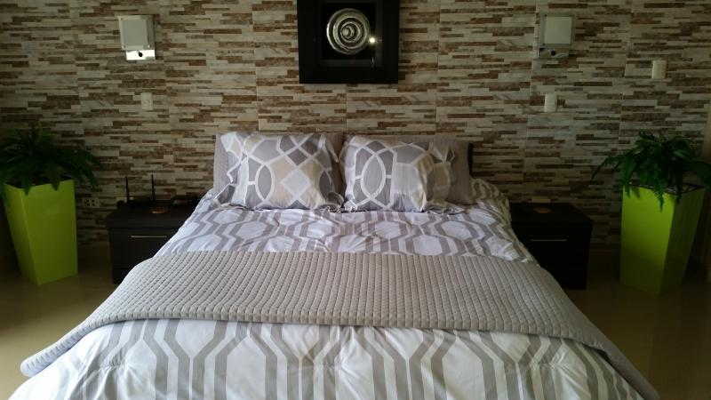 Master Bedroom with sconces and end tables.  Ensuite bathrooms in each bedroom