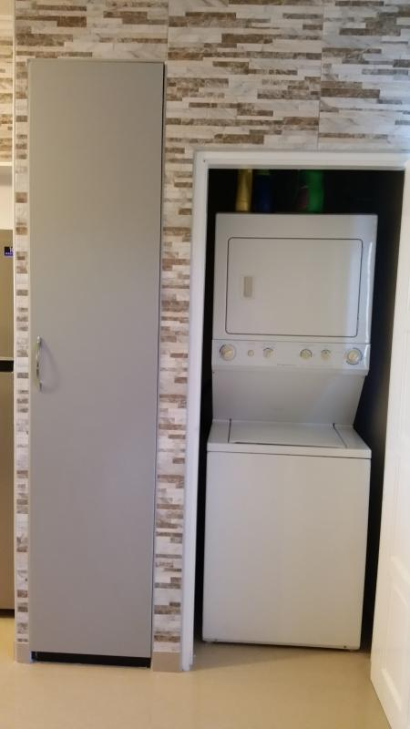 Stacked washer/dryer.  That's a tall closet next to it with cleaning agents and accessories