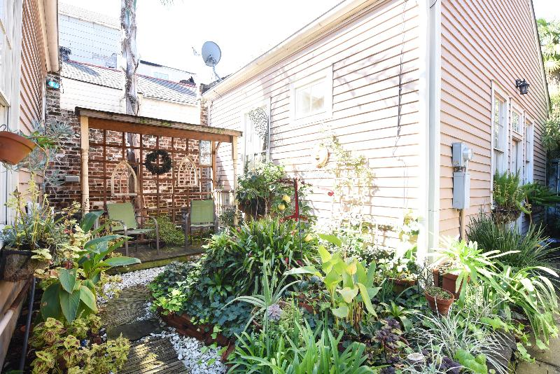 Garden includes covered porch, ideal for morning coffee or evening cocktails.