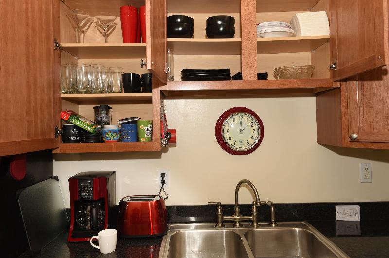 Kitchen cabinets are well stocked with everything needed for cooking and serving.