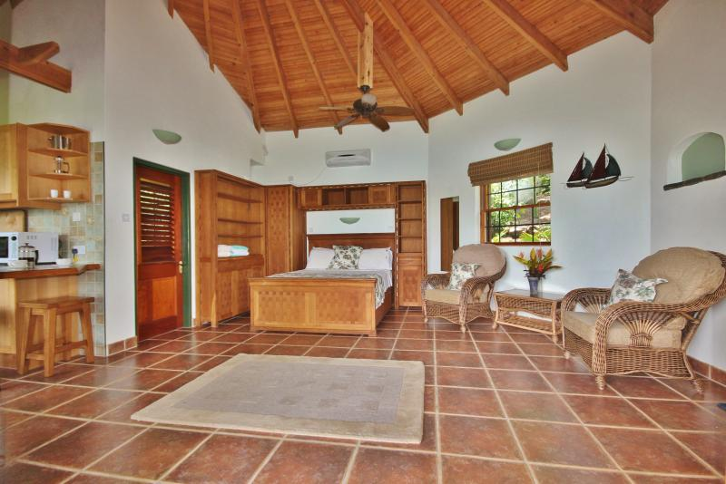 The spacious bedroom and living area of Palm Cottage