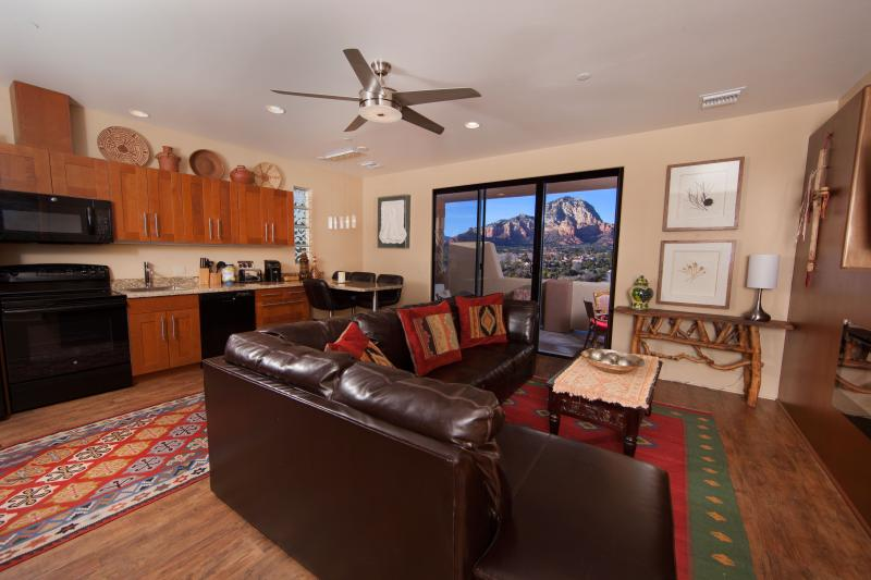 The Living Room has a full kitchen, dining area for four, leather sectional, and electric fireplace.