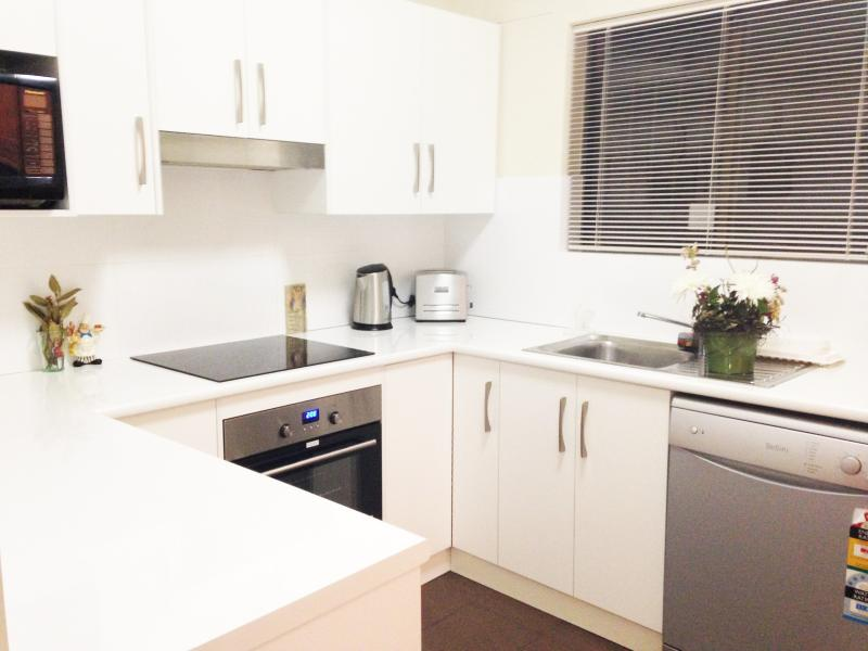 New white kitchen with fridge, microwave, dishwasher, cooktop and oven.  Fully stocked.