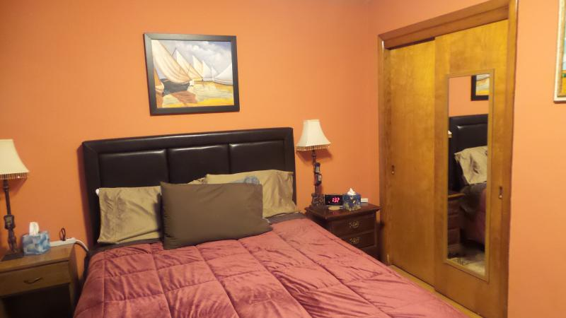 orange bed room with queen bed and tv uses two remotes
