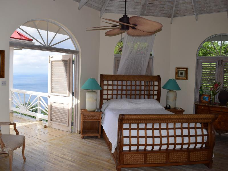 Queen-sized sleigh bed in guest bedroom, with double doors with view of Pitons