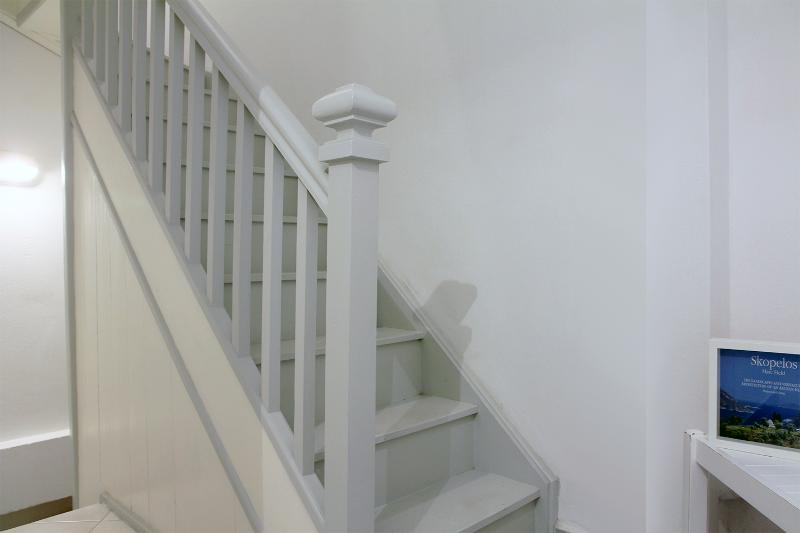 From middle floor hallway, the wooden stairway continues to the top level of the house.