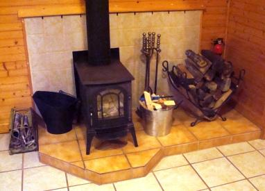 Wood burning stove in living room with glass door for fire viewing.