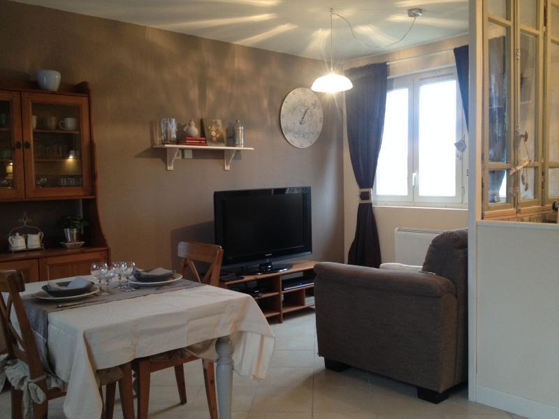 Le séjour dispose d'une table pour deux convives, d'un espace salon avec tv écran plat et canapé