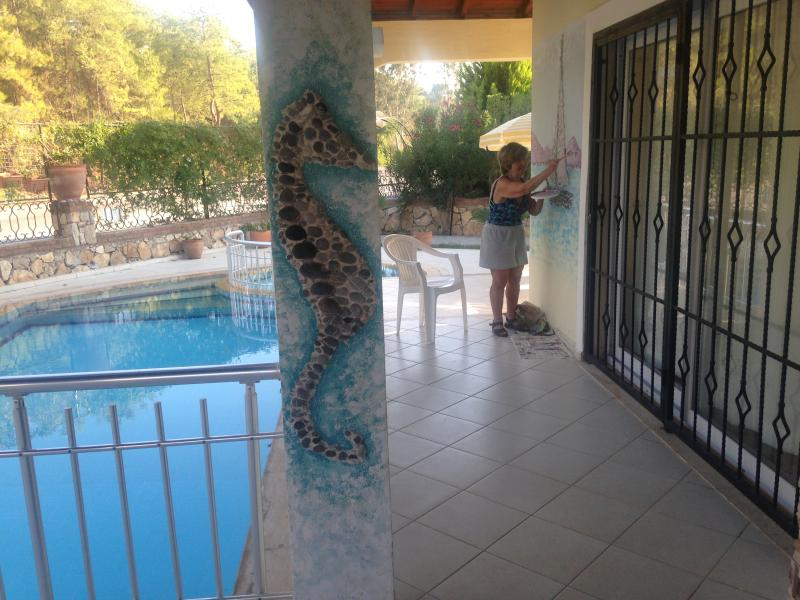 I love enhancing our beautiful villa, inside and out. Here I am creating a mural made of sea pebbles