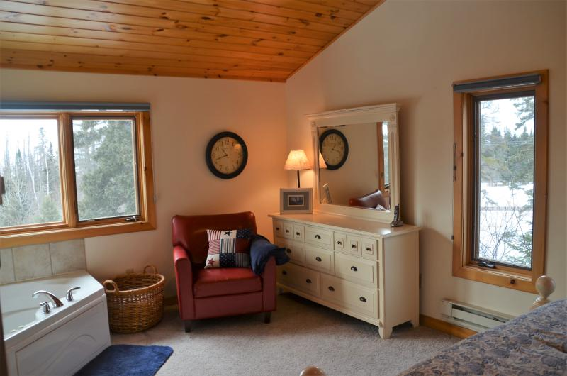 There is a cozy chair for reading and pretty views out every window in the master bedroom.