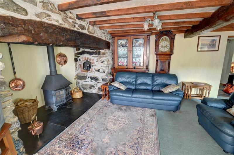The sitting room also has a beamed ceiling, and a woodburning stove in the large beamed inglenook fireplace