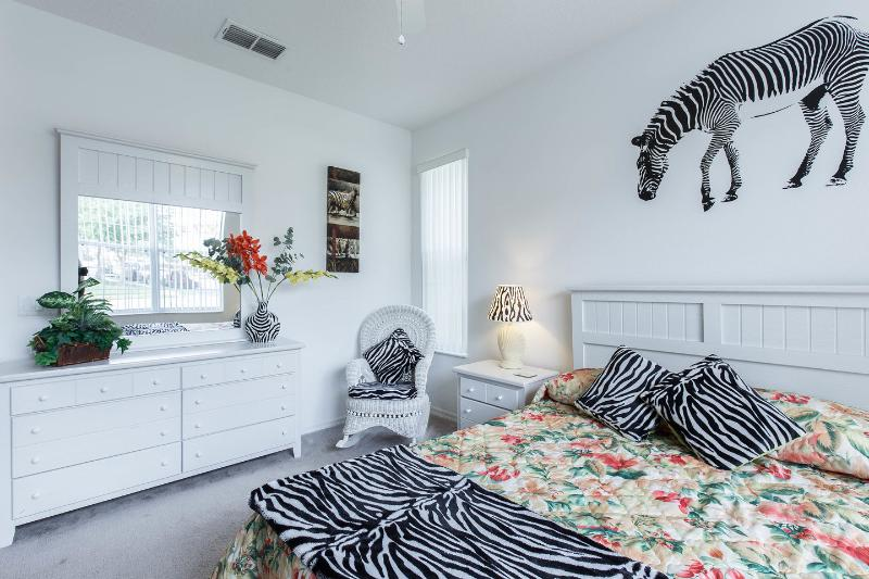 The downstairs master bedroom features a wicker rocking chair and dressing table with 6 drawers.