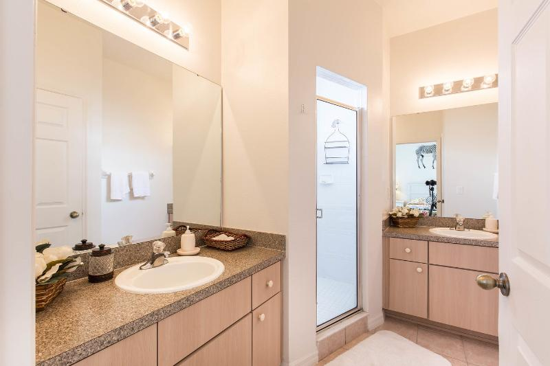 Downstairs master bedroom suite featuring his and hers sinks, walk-in shower and separate restroom.
