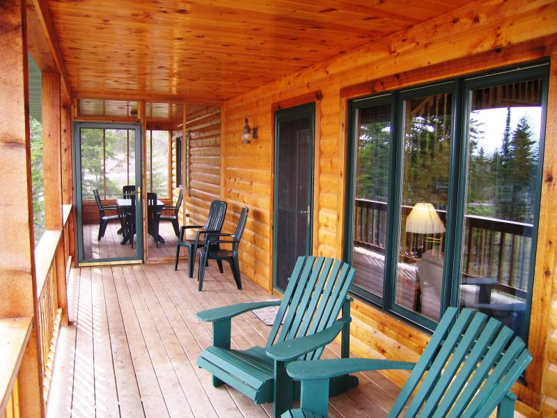 Covered deck and screen porch offer a view of woods and Lake Superior