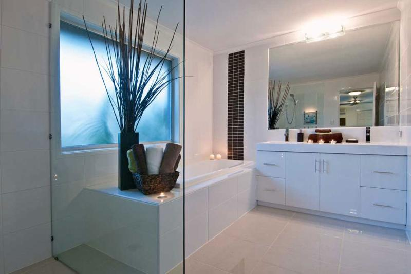 Large sparkling bathroom with shower and double sink unit.