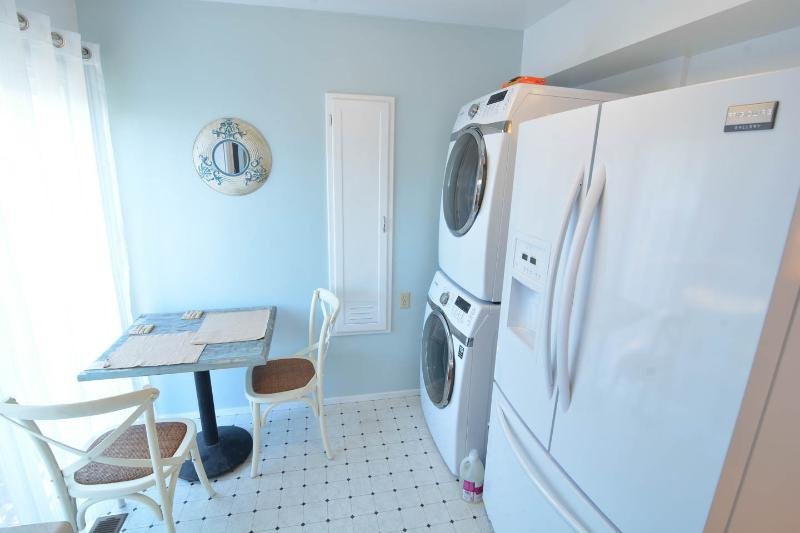 Steam washer and dryer next to the fridge in the kitchen.