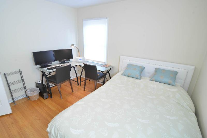 Second bedroom includes a queen bed and desk.
