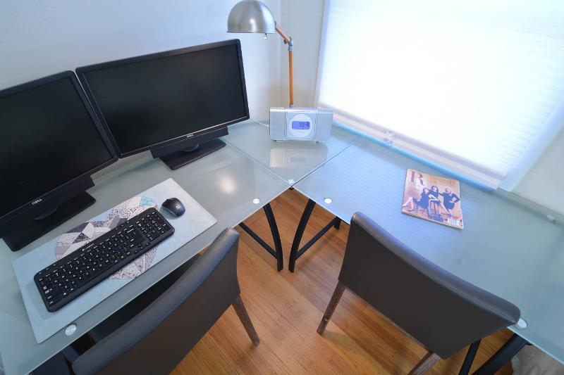 Desk for two including computer with dual monitor in second bedroom.