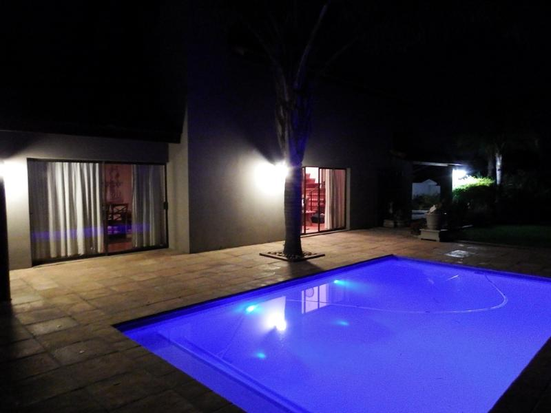 Pool at night. Two sliding doors leading out to the pool and gazebo area.
