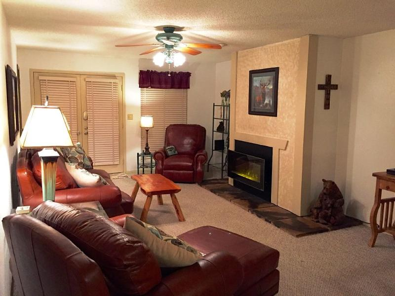 Living room with picture of electric fireplace, electric recliner and chair and ottoman.