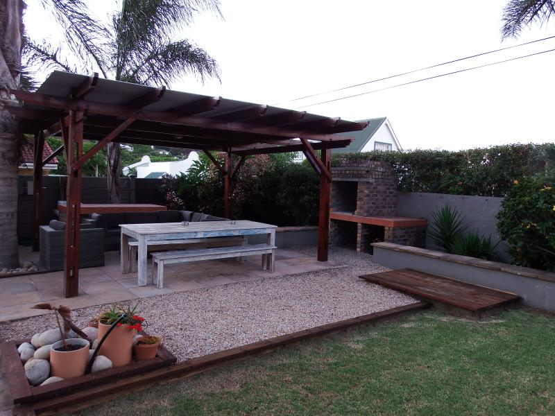 Gazebo and outside entertainment/barbecue area next to swimming pool and large outside dining table.