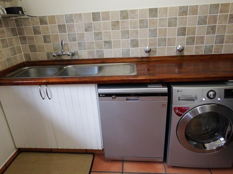 Separate scullery with dish washing machine and washing machine/tumble dryer combination.