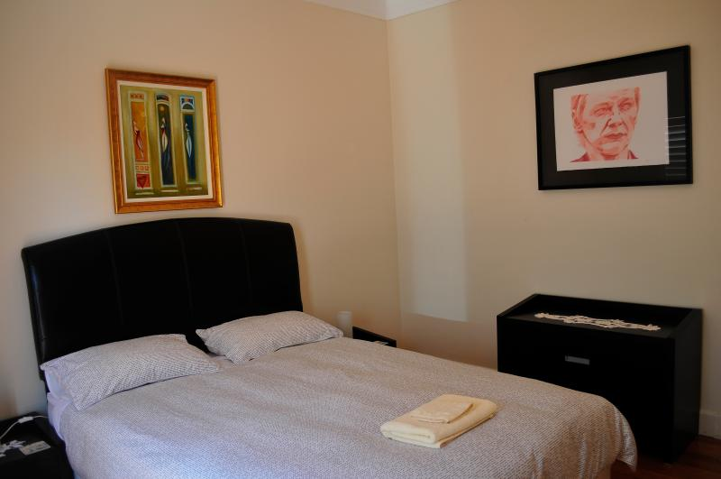 Bedroom with queen size bed and access to outdoor entertainment area with ocean views