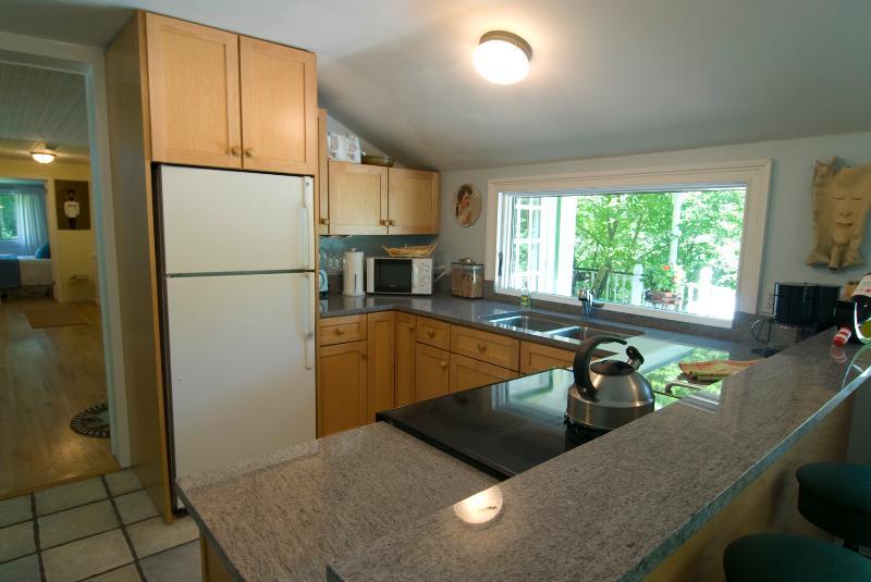 Kitchen with kitchen window overlooking deck and stream