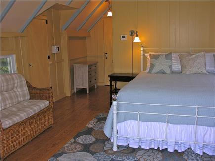Master suite is large with king bed, wicker settee, and numerous antiques