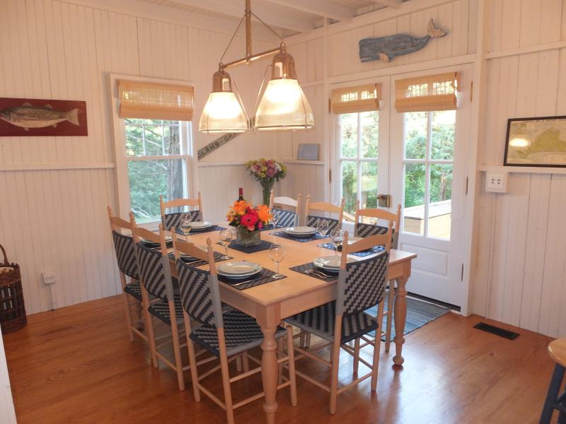 Custom maple farm table seats 8 and hand woven chairs. Double french doors open to the back deck