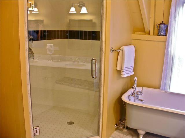 Large shower with seat and hand held shower head. Original 1800's claw foot tub!