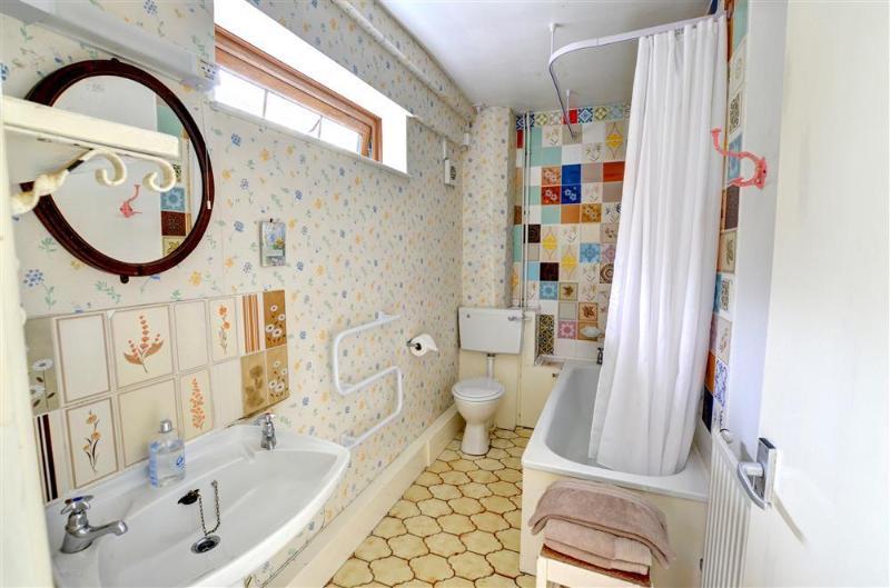 La salle de bain lumineuse et colorée dispose d'une douche dans la baignoire