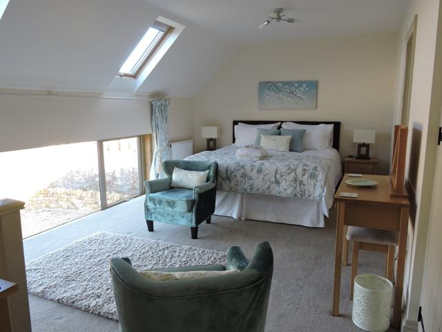 Upstairs is the huge bedroom with ensuite bathroom and separate seating area