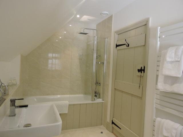 The large ensuite bathroom has a full size bath with power shower over. Towels are provided.