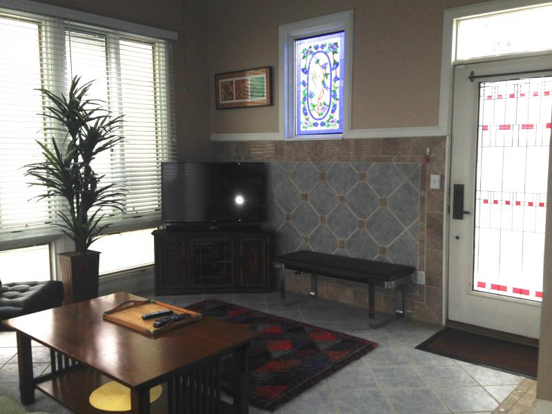 Living Room showing tile floor, wall, smart TV w/ssurround sound & dvd, entry stained glass door