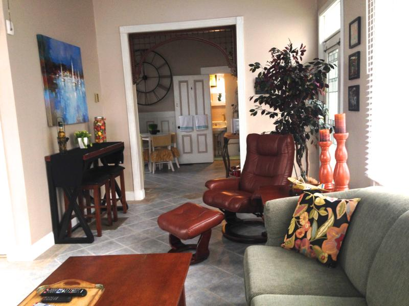 Living Room toward kitchen with leather contemporary recliner, black convertible dining table