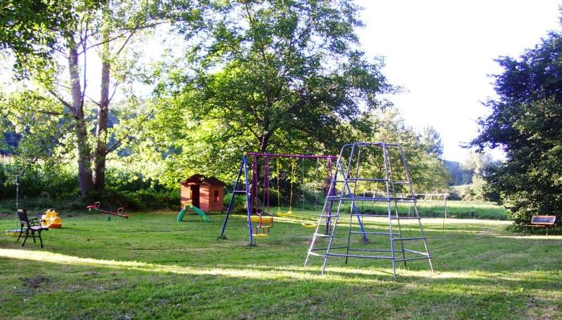 Outdoor playground with swings,slide, a climbing frame, wooden play house,football net and badminton