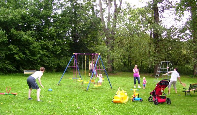 Jogar beisebol ou futebol no parque infantil ao ar livre .Ele tem baloiços, escorregas, um baloiço,