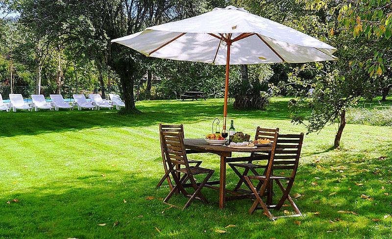 O jardim exterior Villa Mimosa com mesa e cadeiras para refeições ao ar livre.