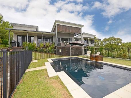 The front of the house with the pool and the verandah