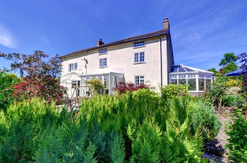 View of front of house with mature gardens, sits in seclusion, offers lovely views of the surrounding peaceful countryside.