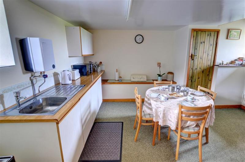 The kitchen diner has fitted units and a circular table and chairs