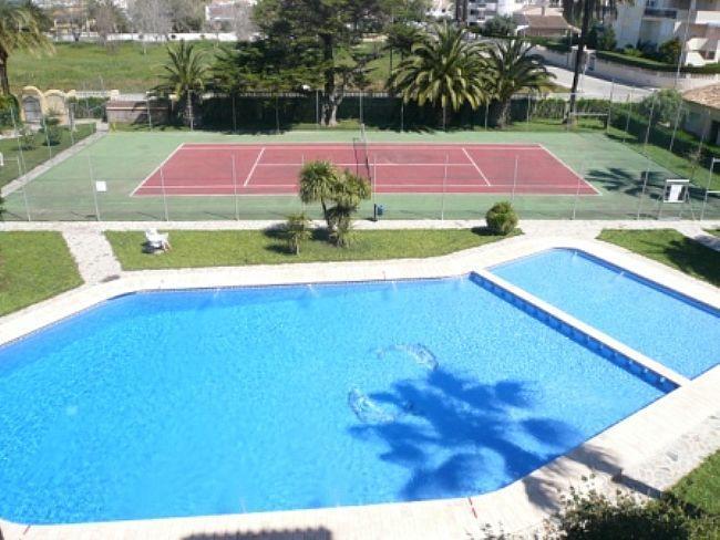 Vista de la piscina y pista de tenis desde el balcón frontal